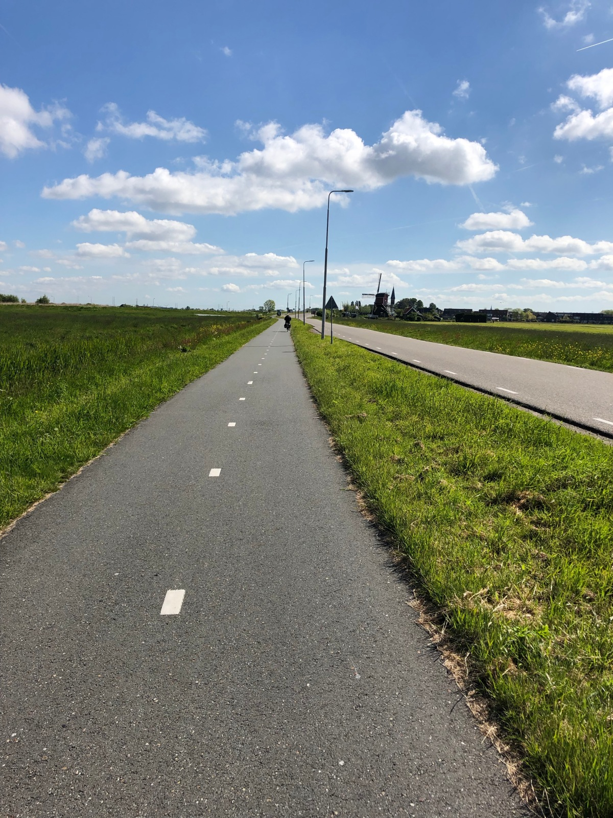 Clear blue Dutch sky. The bike path with the road on the right.