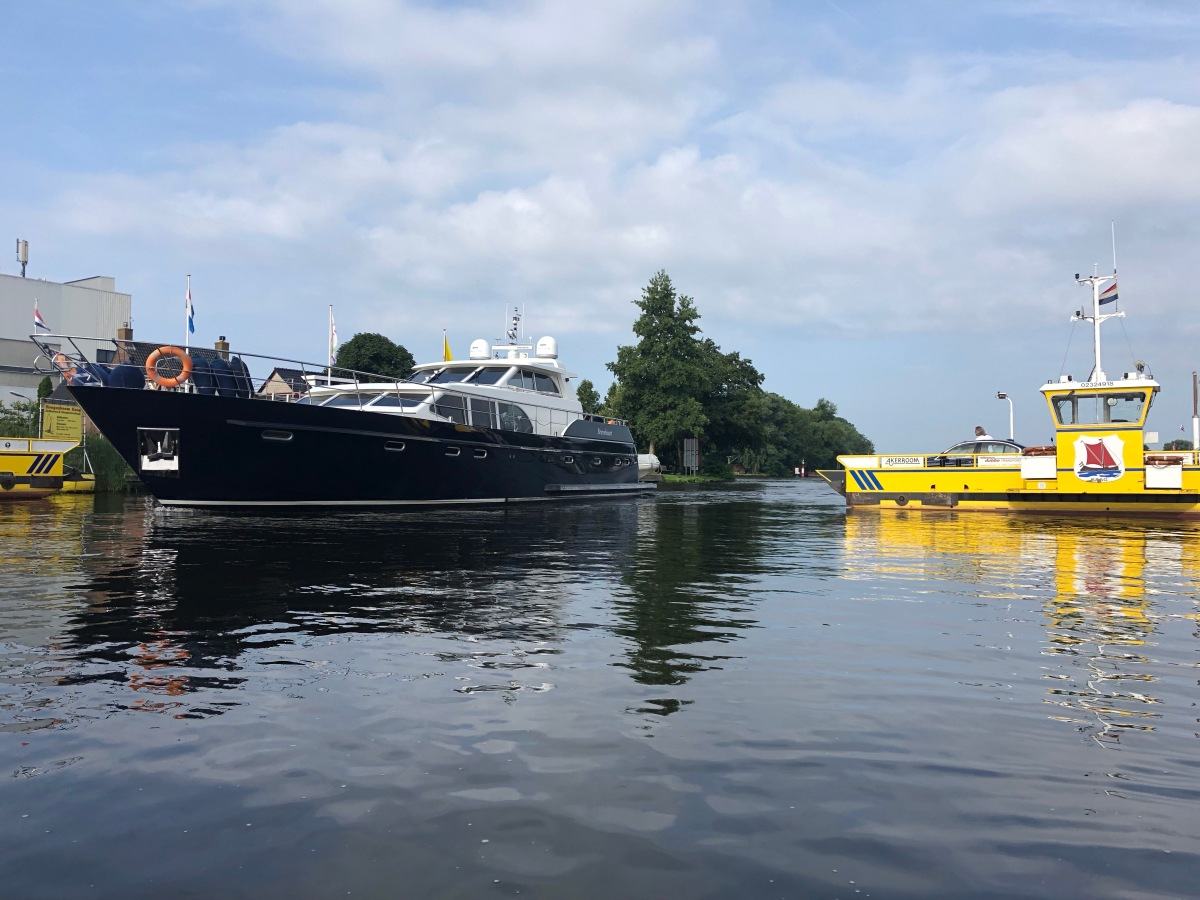 Busy morning on the Ringvaart- A yacht and the yellow car ferry.